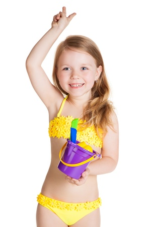 little blonde happy girl in yellow swimsuit holding toy purple bucket over white background Stock Photo