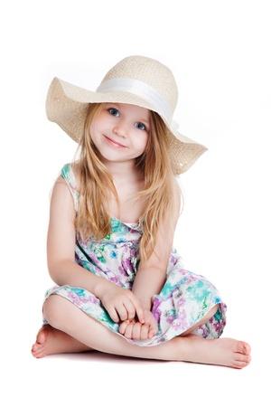 kleine blonde Mädchen mit großen weißen Hut und Kleid sitzt auf dem Boden auf weißem Hintergrund
