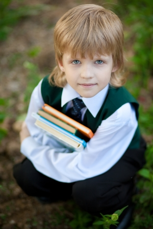 little boy in suit holding four books  Stock Photo