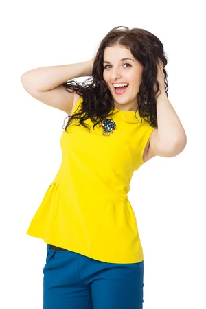 beautiful brunette happy girl with curly hair wearing yellow blouse and blue pants over white background