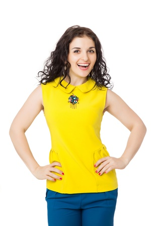 beautiful brunette happy  girl with curly hair wearing yellow blouse and blue pants over white background  Stock Photo