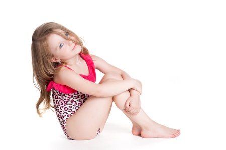 little blonde happy girl in pink swimsuit over white background sitting on the floor