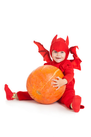 little boy in red devil costume sitting and holding big pumpkin over white background