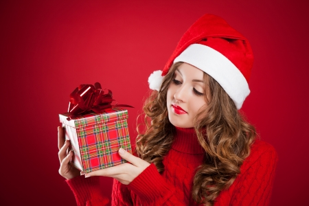 beautiful brunette girl in red sweater holding Christmas present wearing Santa Clause hat