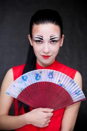 portrait of a geisha woman with blue fan