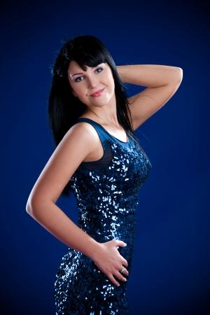 beautiful brunette girl in shining dress over dark background Stock Photo