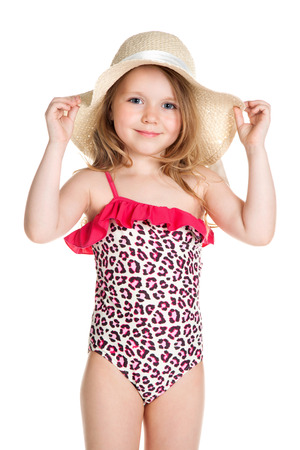 little blonde happy girl in pink swimsuit holding hat over white background