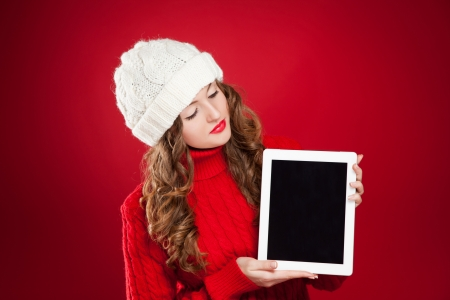 beautiful brunette girl wearing red sweater and holding ipad over red background  photo
