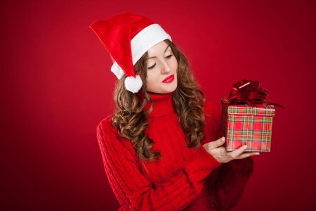 santa clause hat: beautiful brunette girl in red sweater holding Christmas present wearing Santa Clause hat