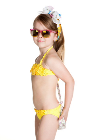 little blonde girl wearing swimsuit, sun glasses and bag over white background  photo