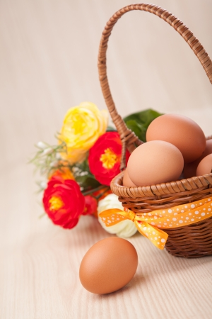 one egg near little basket with ribbons and flowers on wooden table