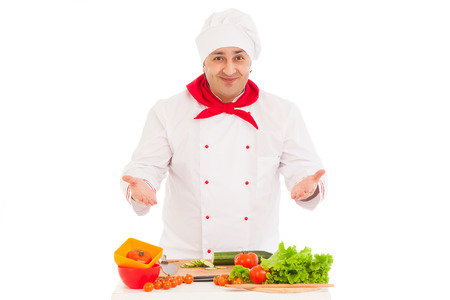 happy chef  cooking with fresh vegetables  wearing red and white uniform over white background