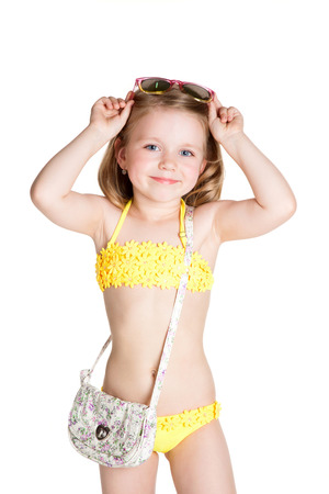 kleines blondes Mädchen mit Badeanzug, Sonnenbrille und Tasche auf weißem Hintergrund