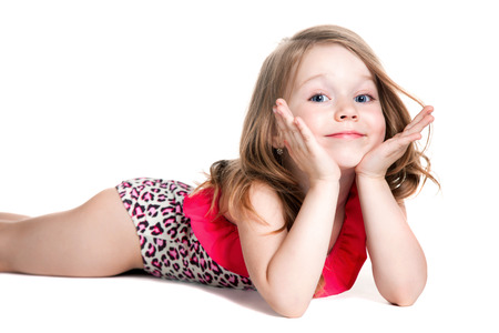 little blonde happy girl in pink swimsuit over white background lying on the floor  photo