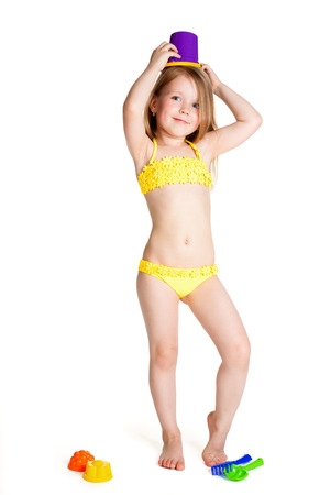 little blonde happy girl in yellow swimsuit holding toy purple bucket over white background photo