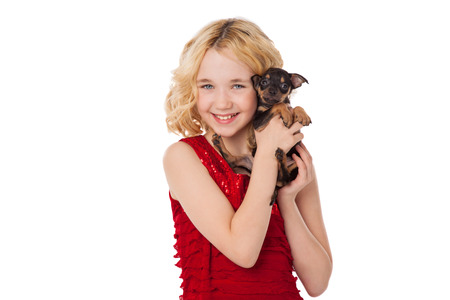 beautiful blonde little girl holding  puppy wearing red dress photo