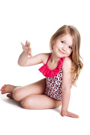 feliz niña rubia en traje de baño de color rosa sobre fondo blanco acostado en el piso Foto de archivo