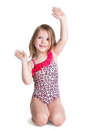 kleine blonde Mädchen glücklich in rosa Badeanzug auf weißem Hintergrund auf dem Boden sitzen