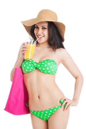 beautiful brunette girl in green swimsuit and hat, holding pink bag and glass of orange juice over white background