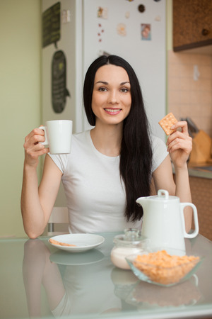 brunette girl drinking tea with cookie in the moring in the kitchen