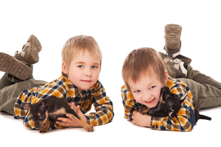 smiling boys hodling puppies lie on the floor over white background