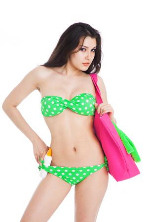beautiful brunette girl wearing green swimsuit holding  bottle of sunscreen over white background Stock Photo