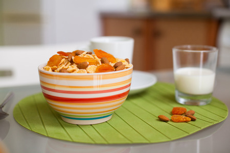 bowl with muesli and a glass of milk on the table in the morning Stock Photo