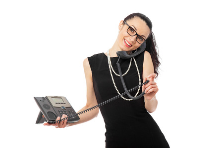 brunette  businesswoman in black dress holding telephone and talking over white background