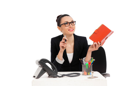 brunette businesswoman sitting in office chair and writing in notebook over white background  photo