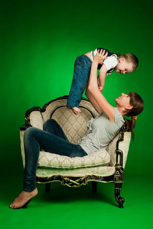 happy mother holding her little boy up sitting in armchair