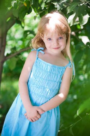 little girl wearing blue dress in the park under trees