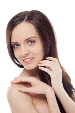 portrait of beautiful brunette smiling girl holding hands on her face over white background Stock Photo