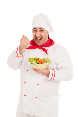 chef  holding dish with salad and fresh vegetables  wearing red and white uniform over white background
