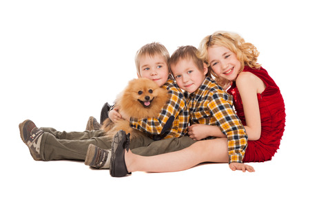 three children playing with little dog sitting on white background. brothers and sister