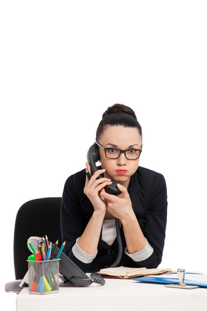 brunette secretary talking on the phone sitting over table isolated on the white Stock Photo