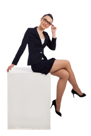 brunette woman in black skirt and jacket sitting on the white cube over white background photo