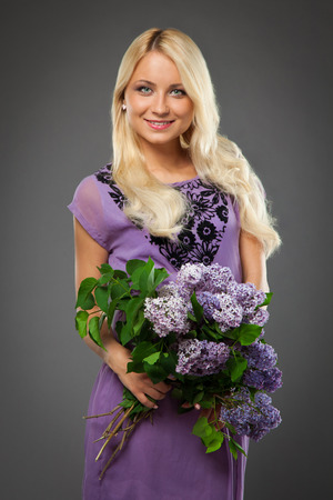 blonde girl in purple dress holding bouquet of lilac over grey background photo