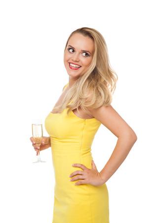 beautiful blonde woman wearing yellow dress drinking champagne isolated on white photo