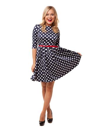 blonde schlanke Mädchen in Dot-Kleid und Schuhe auf weißem Hintergrund
