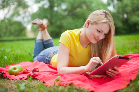 blonde girl lying in the park with tablet on the red coverlet. summer  photo
