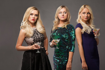 bachelorette party: three blonde girls wearing evening dresses driknking martini over grey background