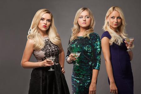 despedida de soltera: tres niñas rubias con vestidos de noche driknking martini sobre fondo gris