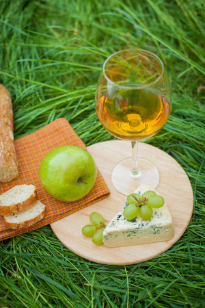 Stillleben mit Weißwein, Baguette, Käse, Trauben und Apfel auf dem Rasen Standard-Bild