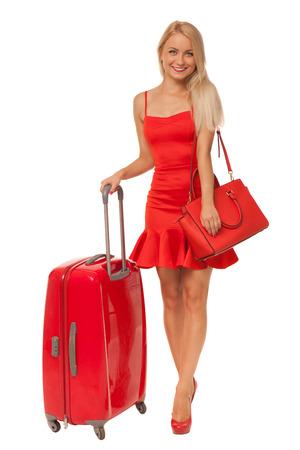 schöne blonde Frau mit rotem Kleid mit großen Tasche und Koffer isoliert auf weiß