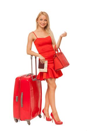 schöne blonde Frau mit roten Kleid mit großen Tasche, Dokumenten und Koffer isoliert auf weiß