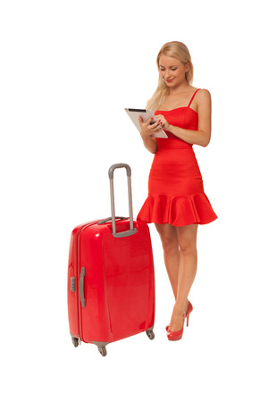 blonde girl wearing red dress holding tablet with big suitcase isolated on white background Stock Photo