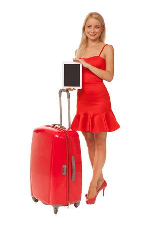 blonde Mädchen tragen roten Kleid holding Tablet mit großem Koffer auf weißem Hintergrund isoliert Standard-Bild