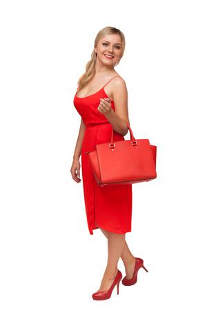 blonde schöne Frau im roten Kleid hält große Tasche isoliert auf weiß