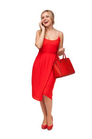 blonde schöne Frau im roten Kleid mit großen Tasche im Gespräch auf dem Handy isoliert auf weiß