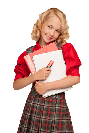 little blonde girl wearing plaid dress holding copy-book and pencils isolated on white